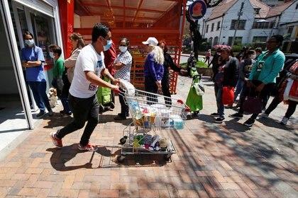 Personas salen de un supermercado usando mascarillas para evitar el contagio con coronavirus en Bogotá, Colombia, 17 de marzo, 2020 (REUTERS/Leonardo Muñoz)
