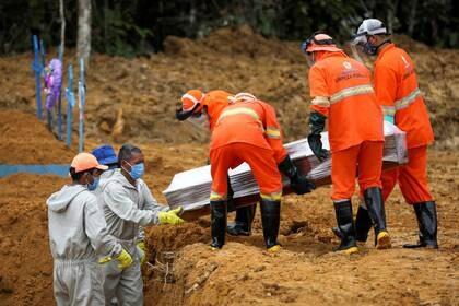Sepultureros llevan un ataúd durante un entierro masivo de personas que fallecieron debido al COVID-19) en el cementerio Parque Taruma en Manaos, Brasil. 13 de mayo de 2020. REUTERS/Bruno Kelly