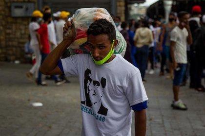 Un joven carga al hombro una bolsa con productos que regala el régimen de Maduro, como parte de pago por asistir a un concierto para pedir la liberación de Alex Saab