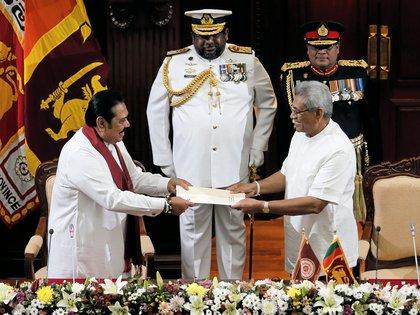 El president Gotabaya Rajapaksa entrega un documento a su hermano, el primer ministro Mahinda Rajapaksa.