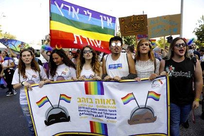"""Los participantes sostienen una pancarta con la traducción al árabe y al hebreo del lema """"Marcha por el orgullo y la tolerancia"""" durante el desfile anual del Orgullo de Jerusalén el 2 de agosto de 2018.  Miles de personas asistieron al desfile en la ciudad bajo una fuerte custodia policial, conscientes de un ataque mortal que ocurrió en 2015 contra los manifestantes"""