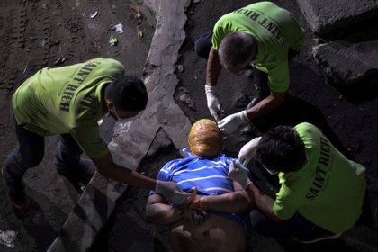 Trabajadores funerarios de Manila retiran la cinta adhesiva de la cabeza y las muñecas de un hombre que la policía dice que fue asesinado por los vigilantes. Estos asesinatos tienen un estilo familiar: vigilantes a menudo llegan en dos o más motos sin placas de matrícula, sus rostros ocultos por cascos y máscaras (Reuters)