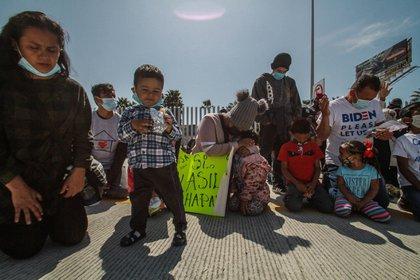 Un grupo de personas migrantes, rezan hoy miércoles, en las inmediaciones del puerto fronterizo del Chaparral ciudad fronteriza de Tijuana.  EFE/Joebeth Terríquez