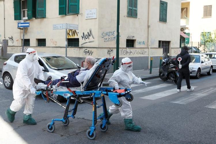 Personal médico vistiendo equipo de protección trasladan a un paciente en una camilla en Italia, en medio de la propagación de la enfermedad por coronavirus (REUTERS)