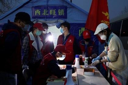 Funcionarios verifican información de personas que ingresan desde la provincia de Hubei a Pekín, China, 25 marzo 2020. cnsphoto vía REUTERS.
