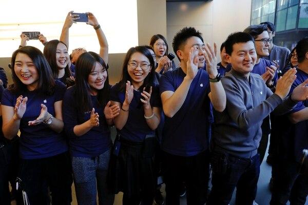 Los vendedores de la tienda de Apple en Beijing felicitas al primer comprador del nuevo iPhone. (REUTERS/Damir Sagolj)