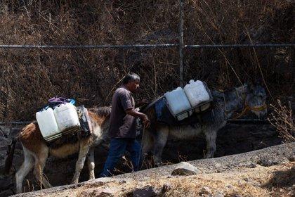 CIUDAD DE MÉXICO, 07ABRIL2021.- Los cargadores se dirigen hacia los domicilios donde los vecinos aún no cuentan con agua entubada.  Foto: Graciela López / Cuartoscuro.com