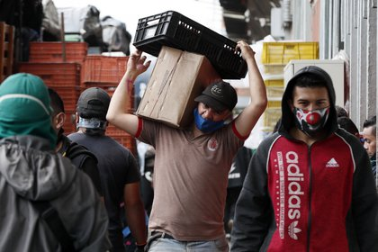 Trabajadores de la plaza de mercado Corabastos usan mascarillas para protegerse de la Covid-19, mientras empacan y trasladan alimentos en Bogotá (Colombia). EFE / Carlos Ortega/Archivo