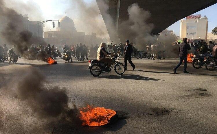 Manifestantes iraníes se manifiestan en medio de la quema de neumáticos durante una manifestación contra un aumento en los precios de la gasolina, en la ciudad central de Isfahan el 16 de noviembre de 2019. (AFP)