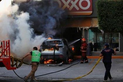 Foto del sábado de bomberos apagando un auto incendiado fuera de una tienda tras un operatvo de autoridades mexicanas contra el crimen organizado en Celaya, estado  Guanajuato.  Jun 20, 2020. REUTERS/Sergio Maldonado