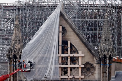 Workers prepare to remove damaged scaffolding elements from the remains of the burnt roof of Notre Dame Cathedral in Paris, France, June 8, 2020. REUTERS/Christian Hartmann