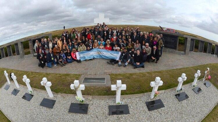 La foto final de las 22 familias junto a la bandera argentina, en pleno corazón del cementerio de Darwin