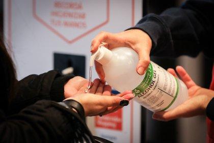 Personas se ponen alcohol en gel en las manos para entrar a un centro comercial, en Montevideo (Uruguay). EFE/Raúl Martínez/Archivo