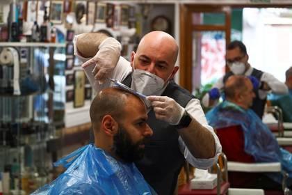 Un peluquero con una mascarilla y guantes corta el pelo a un cliente en la barbería más antigua de Madrid, durante el primer día de reapertura durante el brote de la enfermedad del nuevo coronavirus (COVID-19), en Madrid, España, el 4 de mayo de 2020. REUTERS/Sergio Pérez