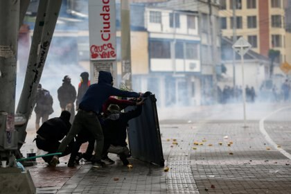 Demonstrators take cover as they clash with riot police during a protest in Bogota, Colombia, November 21, 2019. REUTERS/Luisa Gonzalez