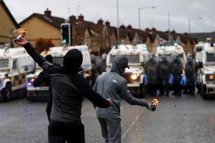 Manifestantes lanzan cócteles Molotov frente a las fuerza de seguridad en Belfast el 8 de abril de 2021 (REUTERS/Jason Cairnduff)