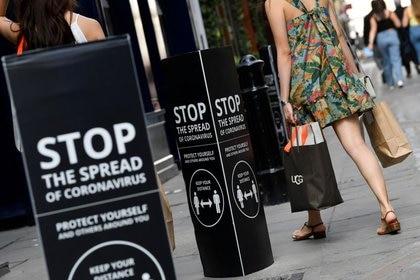 FOTO DE ARCHIVO. Compradores caminan junto a carteles de distanciamiento social en el distrito comercial y de restaurantes de Covent Garden, en medio de la propagación de la enfermedad del coronavirus (COVID-19), en Londres, Reino Unido. 2 de agosto de 2020. REUTERS/Toby Melville