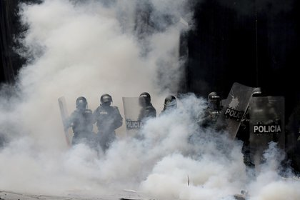 Varios policías se ven inmersos en una nube de gas lacrimógeno tras dispersar a manifestantes en la Plaza Bolívar, en el centro de Bogotá, Colombia, el jueves 21 de noviembre de 2019. (AP Foto/Fernando Vergara)