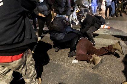 Un manifestante es ayudado por otros después de ser herido por una bomba de gas lacrimógeno frente a la estación de policía de Brooklyn Center mientras la gente se reúne para protestar después de que un oficial de policía disparó y mató a un hombre negro en Brooklyn Center, Minneapolis, Minnesota el 11 de abril de 2021. (Photo by Kerem Yucel / AFP)