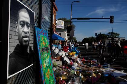 Una fotografía del rostro de George Floyd en el improvisado homenaje que realizaron vecinos de Minneapolis en la esquina donde fue asesinado (REUTERS/Carlos Barria)