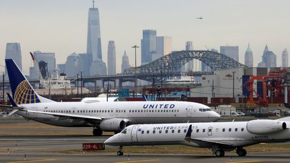 FILE PHOTO: United Airlines passenger jets taxi with New York City as a backdrop, at Newark Liberty International Airport, New Jersey, U.S. December 6, 2019. REUTERS/Chris Helgren/File Photo