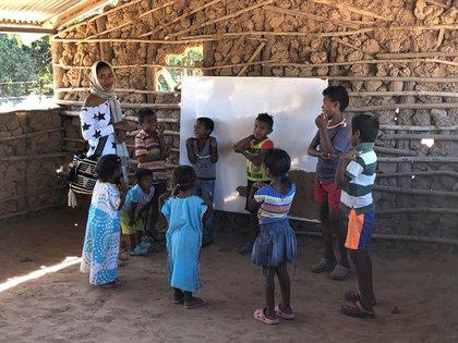 Niños juegan con su profesora en un pueblo indígena wayuu en Colombia. EFE/Adaya González