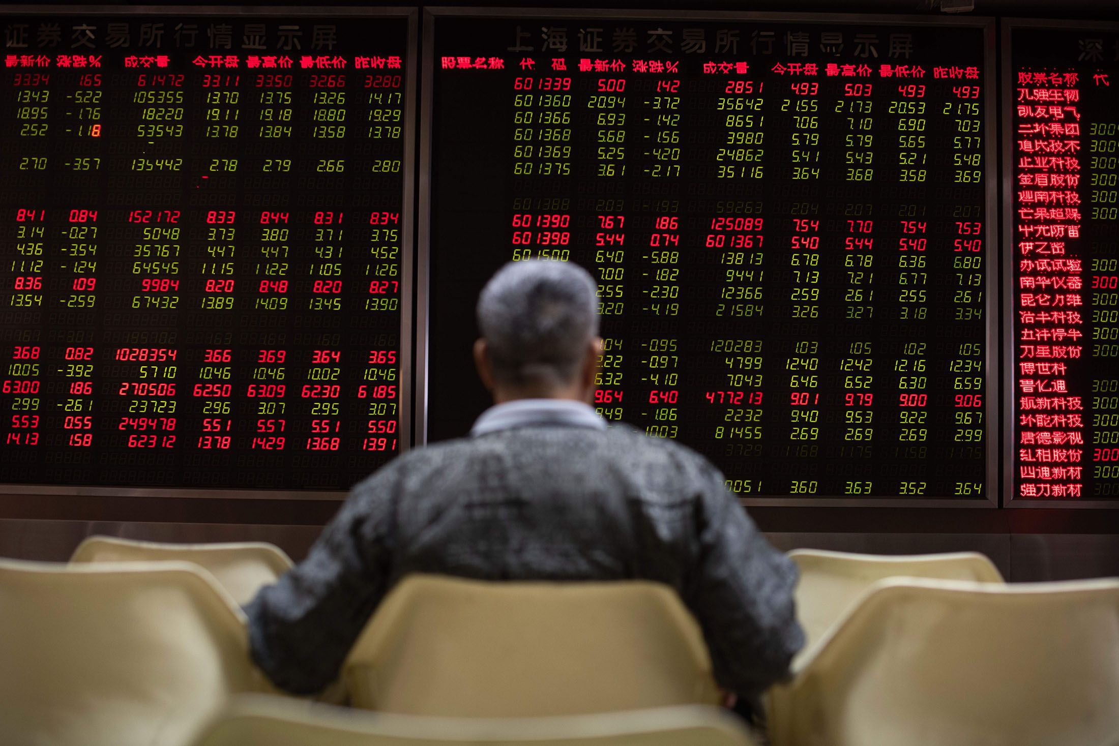 An investor looks at stock price movements on screens at a securities company in Beijing. Photographer: Nicolas Asfouri/AFP/Getty Images