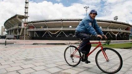 """Foto de archivo. Un hombre monta en bicicleta en los alrededores del estadio Nemesio Camacho, """"el Campín"""" de Bogotá, Colombia [28 de mayo de 2007] (Reuters/ Daniel Muñoz)"""