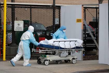 Foto del jueves de trabajadores médicos trasladando el cuerpo de una persona que murió como consecuencia del coronavirus a la morgue del Wyckoff Heights Medical Center en Brooklyn [abril, 2 de 2020] (Reuters/ Brendan Mcdermid)