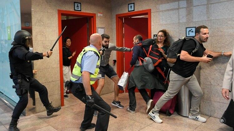 La policía utilizó sus bastones para desalojar la terminal 1 del aeropuerto El Prat, uno de los de mayor tránsito de España (AFP)