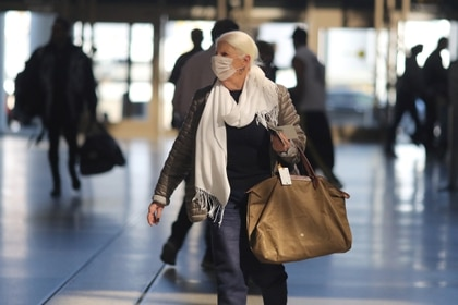 Una mujer camina en el aeropuerto de California con una mascarilla