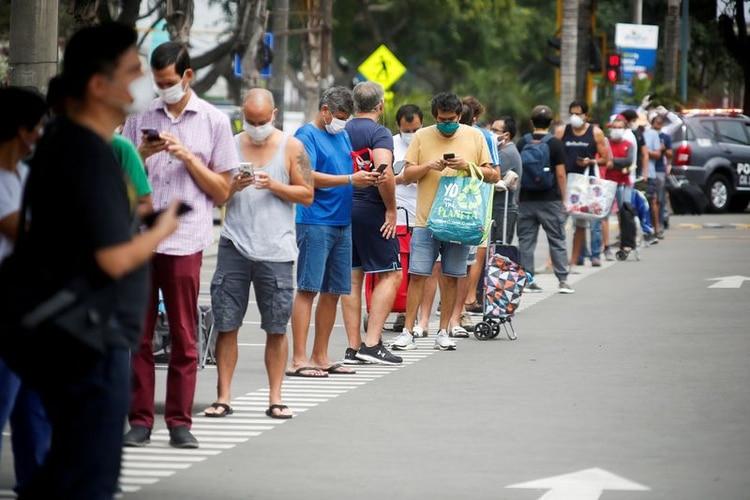 Hombres haciendo una fila para comprar en una tienda en Lima, Perú (REUTERS/Sebastian Castañeda)
