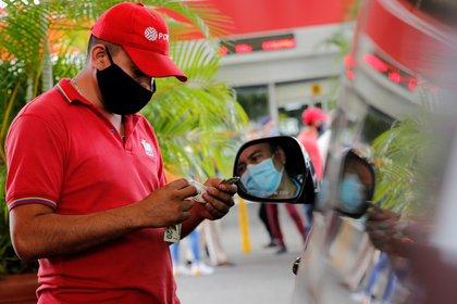 Un empleado que usa una mascarilla protectora cuenta el dinero en una estación de servicio después de que el gobierno de Venezuela lanzó un nuevo sistema de precios de combustible, en Caracas, Venezuela, el 1 de junio de 2020. (REUTERS / Manaure Quintero)