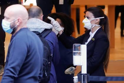 Una persona reparte mascarillas en la entrada de un Apple store, en Zurich, Suiza (REUTERS/Arnd Wiegmann)