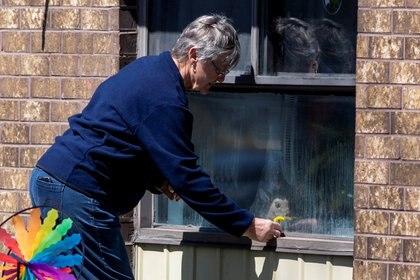 Una mujer deja una pequeña flor para su pariente en la Residencia de Jubilación Orchard Villa, en Ontario