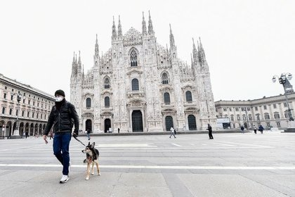 Un hombre con mascarilla con un perro en la plaza del Duomo, Milán, Italia, 10 marzo 2020. REUTERS/Flavio Lo Scalzo