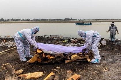 Hombres con trajes de protección colocan un paño blanco sobre el cuerpo de un familiar, fallecido por la enfermedad del coronavirus (COVID-19), antes de su cremación a orillas del río Ganges en Garhmukteshwar en el estado de Uttar Pradesh, India