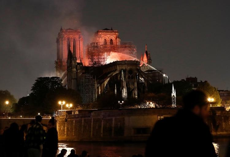 Los bomberos trabajando durante la noche y madrugada para sofocar las llamas. (REUTERS/Benoit Tessier)
