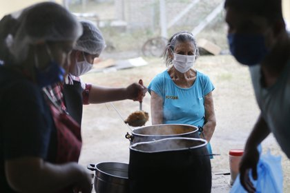Una mujer espera a recibir un plato de comida para ella y su familia en un comedor social durante la pandemia coronavirus en Luque, Paraguay, el lunes 11 de mayo de 2020. (AP Foto/Jorge Sáenz)