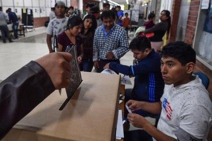 Un ciudadano boliviano residente en Brasil vota para las elecciones presenciales bolivianas en San Pablo (NELSON ALMEIDA / AFP)