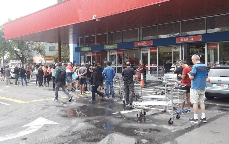 Las personas deben esperar su turno para ingresar a los supermercados (foto Maximiliano Luna)