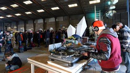 Un DJ pone música durante la fiesta en el hangar de Lieuron que provocó incidentes con la policía de la prefectura de Ille-et-Vilaine. (Photo by JEAN-FRANCOIS MONIER / AFP)