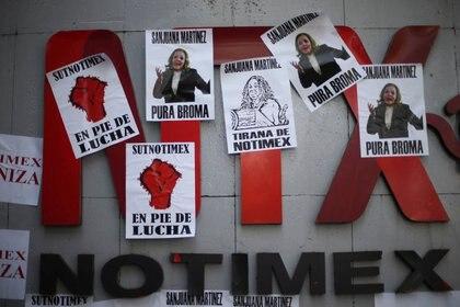 Volantes que representan como un payaso a la directora de Notimex, Sanjuana Martínez, fueron colocados sobre el logotipo de la agencia estatal de noticias mexicana durante una huelga afuera de su edificio en Ciudad de México (Foto: Reuters)