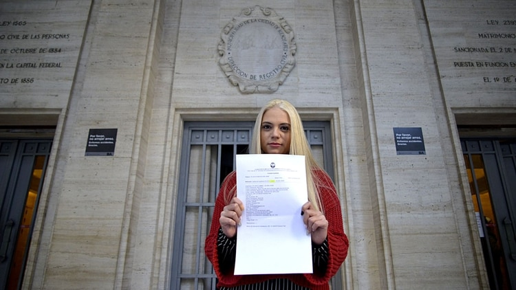 Florencia con la constancia del cambio de apellido en la puerta del Registro Civil (Gustavo Gavotti)