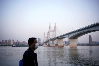 Un hombre con una mascarilla bajo un puente del río Yangtsé en Wuhan después de que se levantara el bloqueo de la ciudad, capital de la provincia de Hubei y epicentro del brote de coronavirus (Reuters)