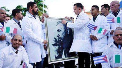 Médicos cubanos sostienen una imagen del fallecido dictador cubano Fidel Castro durante una ceremonia de despedida antes de partir a Italia para ayudar al país europeo, en medio de la pandemia de coronavirus, en La Habana, Cuba. 21 de marzo de 2020 (REUTERS/Alexandre Meneghini)