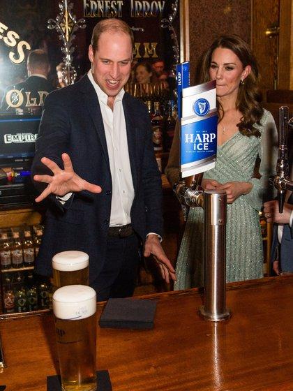 Kate, duquesa de Cambridge, observa al príncipe William quien parece abalanzarse sobre pinta de cerveza durante una visita al Empire Music Hall, Belfast, Irlanda del Norte, en febrero de 2019. Un medio norteamericano publicó que el príncipe estaría bebiendo más de lo recomendable para escapar a sus problemas (Reuters)