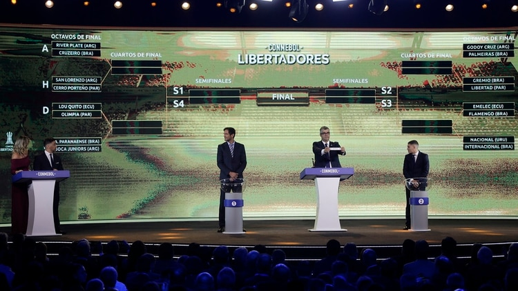 Conmebol Competitions Director Frederico Nantes, second right, holds the paper with the name of a team during Copa Libertadores drawing ceremony at Conmebol museum, in Luque, Paraguay, Monday, May 13, 2019. (AP Photo/Jorge Saenz)