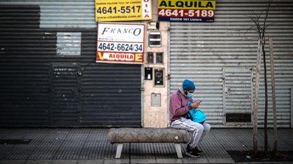 Un hombre revisa su celular frente a locales comerciales cerrados este miércoles, en Buenos Aires (Argentina). EFE/ Juan Ignacio Roncoroni