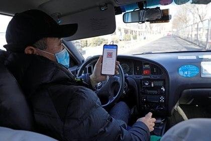 Un taxista muestra un código QR de registro de salud para que un pasajero lo escanee antes de un viaje, luego de nuevos casos de la enfermedad por coronavirus (COVID-19) en el país, en Beijing, China, el 11 de enero de 2021 (REUTERS / Tingshu Wang)
